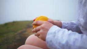 Het meisje eet fruit tijdens een reis aan de bergen stock videobeelden