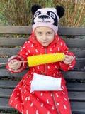 Het meisje eet gekookt graan op een bank in het park stock foto's