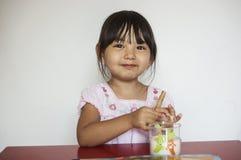 Het meisje eet koekje en melk Royalty-vrije Stock Foto