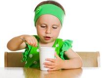 Het meisje eet met een lepel zuivelproduct. Stock Fotografie