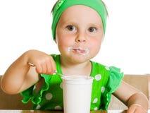 Het meisje eet met een lepel zuivelproduct. Stock Afbeelding