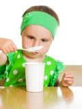 Het meisje eet met een lepel zuivelproduct. Stock Afbeeldingen