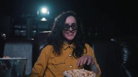Het meisje eet popcorn in de bioskoop stock video