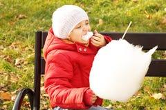 Het meisje eet snoepjes in het park Royalty-vrije Stock Afbeeldingen
