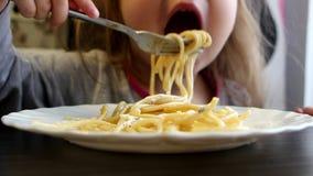 Het meisje eet spaghetti stock footage
