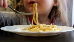 Het meisje eet spaghetti stock video