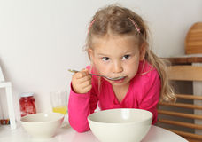 Het meisje eet thuis soep Stock Afbeeldingen