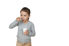 Het meisje eet yoghurt op witte achtergrond wordt geïsoleerd die Royalty-vrije Stock Fotografie