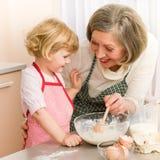 Het meisje en de grootmoederbakselcake van het kind Royalty-vrije Stock Fotografie