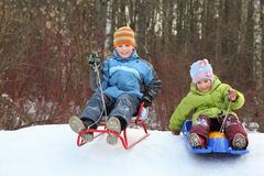 Het meisje en de jongen gaan naar beneden van heuvel op sleeën royalty-vrije stock fotografie