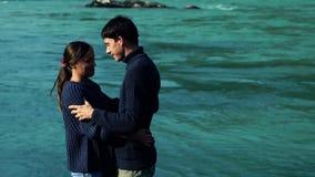 Het meisje en de jongen hugg op de achtergrond van blauw water, bekijken dan elkaar en kus stock footage