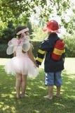 Het meisje en de Jongen kleedden zich als Fee en Brandweerman royalty-vrije stock foto