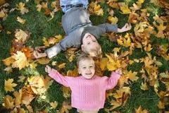 Het meisje en de jongen liggen op gras Stock Foto's