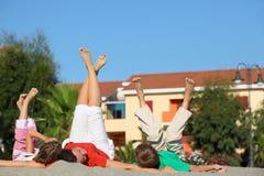 Het meisje en de jongen met moeder het zijn gelogen ruggen op zand stock foto's
