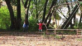 Het meisje en de jongen met zijn moeder werpen op bladeren stock videobeelden