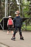 Het meisje en de jongen worden gerold op rollen Stock Afbeelding