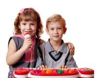 Het meisje en de jongen zingen en spelen Royalty-vrije Stock Foto's