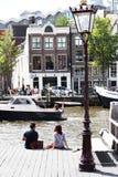 Het meisje en de jongen zitten op een pijler het letten op botenpas py op Amstel Stock Foto's