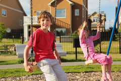 Het meisje en de jongen zitten op schommeling dichtbij plattelandshuisje Royalty-vrije Stock Foto's