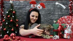 Het meisje en de kat onder de Nieuwjaar` s giften stock footage