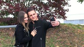 Het meisje en de kerel maken gezamenlijke selfie stock video