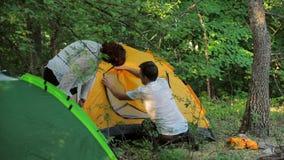 Het meisje en de man plaatsen de tent in vergankelijk stock videobeelden