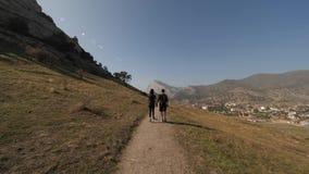 Het meisje en de mens gaan op de bergen stock video