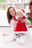 Het meisje en de moeder het vieren van de baby Kerstmis Stock Foto