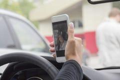 Het meisje en de telefoon in de auto Stock Fotografie
