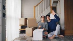 Het meisje en de vriend spreken het maken van plannen rond zittend op vloer van nieuw gekocht huis, kijkend en uitdrukkend stock video
