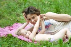 Het meisje en haar moeder ontspannen in het park Royalty-vrije Stock Foto's