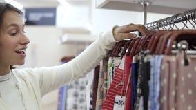 Het meisje is enthralled met verschillende steekproeven van kleur gedrukte stoffen op de hangers en kiest één variant textiel stock videobeelden