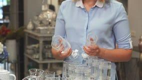 Het meisje evalueert de kwaliteit van glazen stock footage