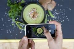 Het meisje fotografeerde haar lunch op een smartphone stock afbeelding