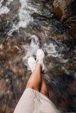 Het meisje fotografeerde hun voeten op de achtergrond van een bergrivier Royalty-vrije Stock Foto