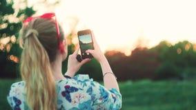 Het meisje fotografeert de zonsondergang op de telefoon achtermening langzame mo stock video