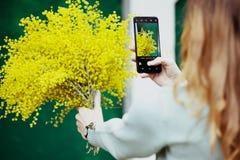 Het meisje fotografeert haar boeket op de telefoon, beeld, technologie, vakantie royalty-vrije stock fotografie