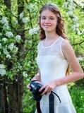 Het meisje fotografeert tot bloei komende boom Stock Afbeeldingen