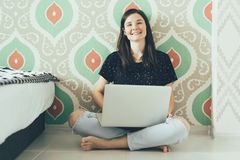 Het meisje freelancer met laptop zit op de vloer en lacht royalty-vrije stock afbeelding