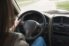 Het meisje gaat achter het wiel van een auto, overhandigt op het stuurwiel Het drijven van een grote auto stock afbeeldingen