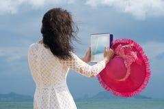 Het meisje gaat en neemt beelden op ipad achteruit royalty-vrije stock foto