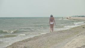 Het meisje gaat langs de kustlijn stock videobeelden