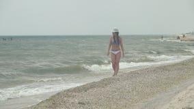 Het meisje gaat langs de kustlijn stock video