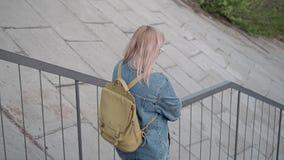 Het meisje gaat onderaan de treden naar de overgang onder de brug Mooi cinematic plan stock footage