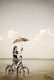Het meisje gaat voor een cyclusrit bij water met paraplu Stock Foto's