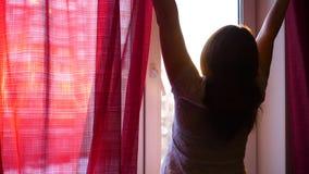 Het meisje gaat vroege ochtend naar het venster, opent de gordijnen De zon` s stralen gaan door het glas over en verlichten de ru stock video