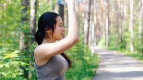 Het meisje gaf zich met water van een fles water stock video