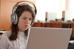 Het meisje gebruikt computer met hoofdtelefoons Royalty-vrije Stock Afbeelding
