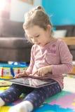 Het meisje gebruikt een digitale tablet Stock Afbeelding