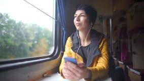 Het meisje gebruikt hoofdtelefoons in de trein door het venster stock footage